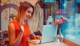woman, freelancer having a video call, online web interview on a laptop in her home kitchen, near window or in a coffee shop, trendy cafe